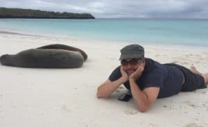 Man in hat and sunglasses lying on a beach in Espanola, holding his chin in his hands