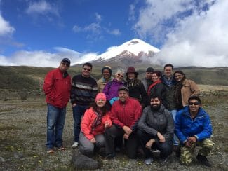 Group of hikers posing with Pichincha volcano in the background