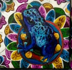 Painting of a blue poison dart frog on a colorful lily pad by Margot Fass
